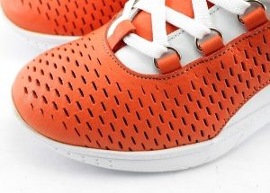 Ladies casual shoes with a fine perforation of the sports soles made in combination of orange and white. Model Cecil.